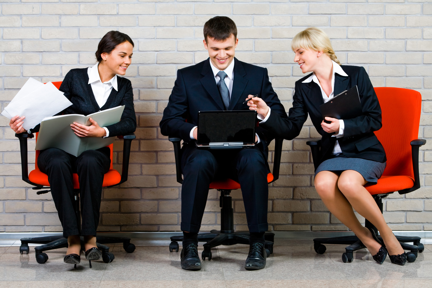 Image of business people sitting on the red armchairs and working on the background of brick wall
